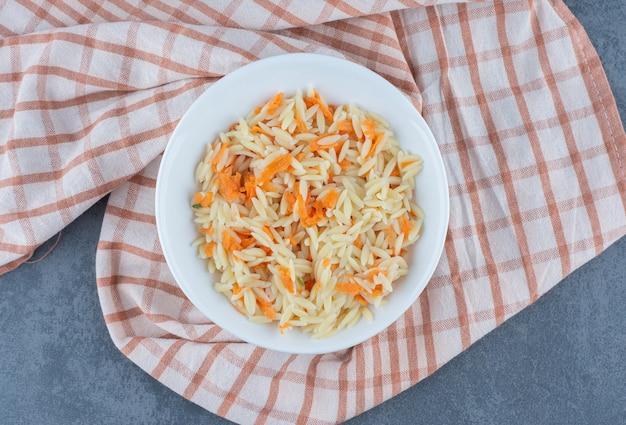 Delicioso arroz com cenoura picada em uma tigela branca.
