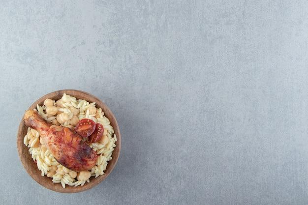 Delicioso arroz com grão de bico e coxa de frango de frango em uma tigela de madeira.