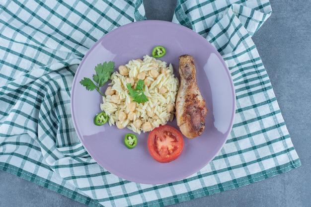 Delicioso arroz com grão de bico e coxinha na placa roxa.