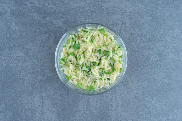 Delicioso arroz com verduras em uma tigela de vidro.