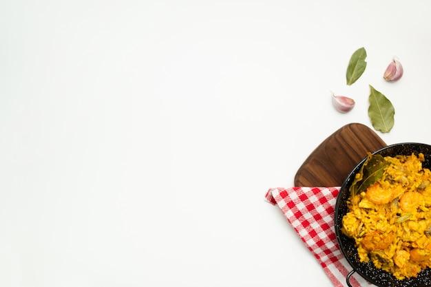 Delicioso arroz espanhol em uma panela de paella no fundo branco, com espaço de cópia