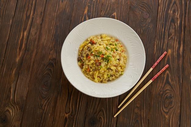 Delicioso arroz frito asiático com carne, ovo, cenoura, alho e cebola verde com pauzinhos vista horizontal de cima no prato branco de mesa de madeira, cópia espaço