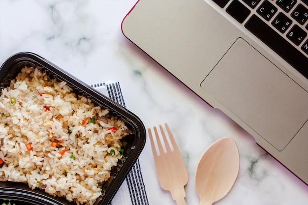 Delicioso arroz frito na lancheira na napery com colher de pau e garfo e computador portátil no local de trabalho