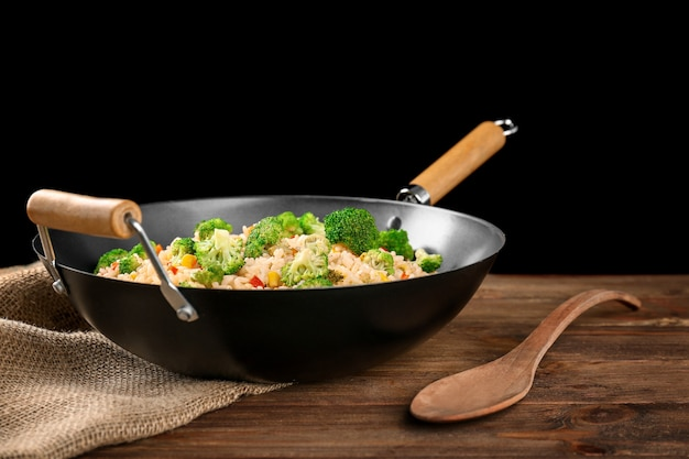 Delicioso arroz pilaf com brócolis na wok na mesa de madeira