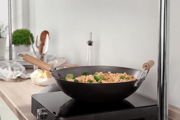 Delicioso arroz pilaf com brócolis na wok no fogão elétrico