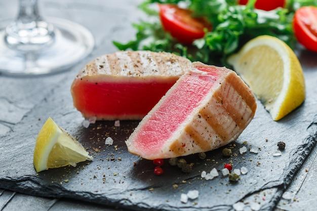 Delicioso atum grelhado com pimenta, limão e salada de verduras e tomates
