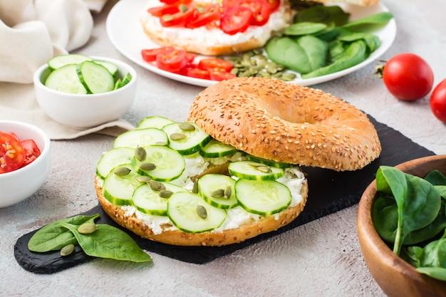 Delicioso bagel recheado com queijo feta, pepino e sementes de abóbora e folhas de espinafre em uma placa de ardósia. lanche saudável light vitamina. fechar-se