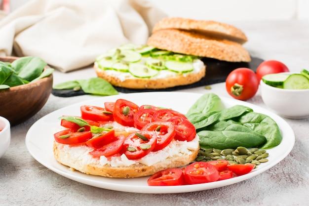 Delicioso bagel recheado com queijo feta, tomate e sementes de abóbora e folhas de espinafre em um prato. lanche leve e saudável de vitamina. fechar-se
