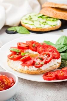 Delicioso bagel recheado com queijo feta, tomate e sementes de abóbora e folhas de espinafre em um prato. lanche leve e saudável de vitamina. visão vertical. fechar-se