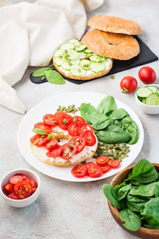 Delicioso bagel recheado com queijo feta, tomate e sementes de abóbora e folhas de espinafre em um prato. lanche leve e saudável de vitamina. visão vertical