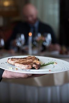 Delicioso bife de porco grelhado, colocado na chapa branca, apresentado a uma pessoa