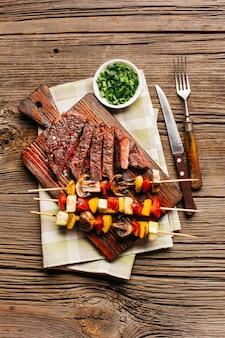 Delicioso bife grelhado e espeto de carne na tábua de madeira sobre o pano de fundo texturizado
