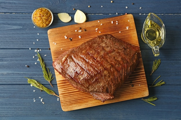 Delicioso bife úmido a bordo e mesa de madeira azul