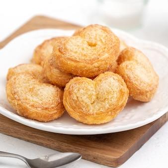 Delicioso biscoito de folhado de borboleta palmier em forma de coração para o conceito de sobremesa de dia dos namorados.