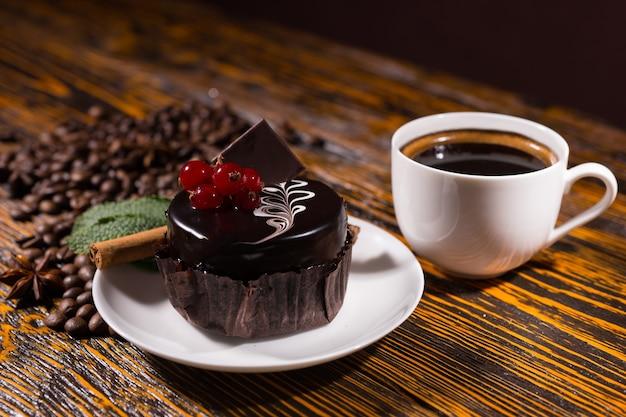 Delicioso bolinho de chocolate amargo decorado com frutas vermelhas por uma caneca de café branca e uma pilha de feijão na mesa de madeira