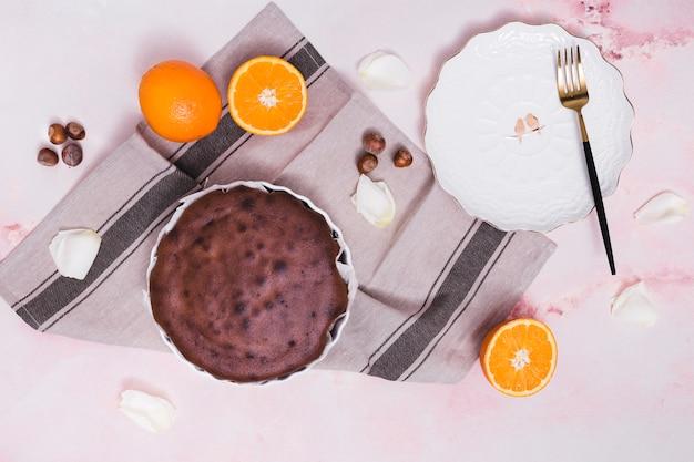 Delicioso bolo assado; avelã; frutas cítricas e pétalas brancas no plano de fundo texturizado