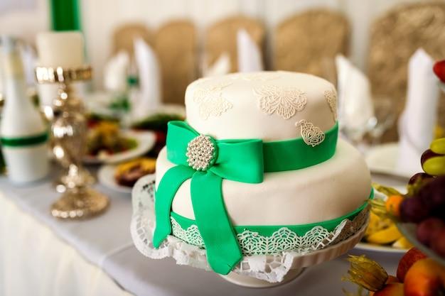 Delicioso bolo branco na forma de um chapéu com fita verde e um laço em cima da mesa