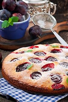 Delicioso bolo caseiro com ameixas numa superfície de madeira