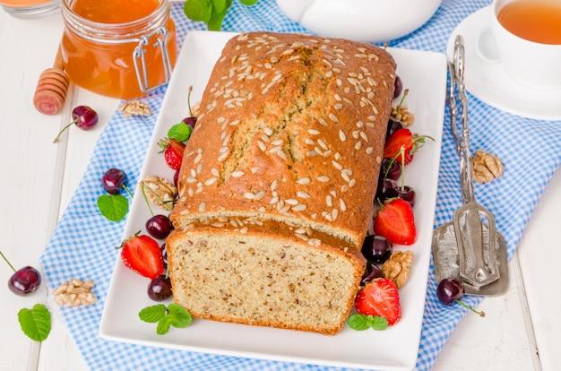 Delicioso bolo caseiro com nozes e sementes de girassol. servido com frutas frescas e mel.