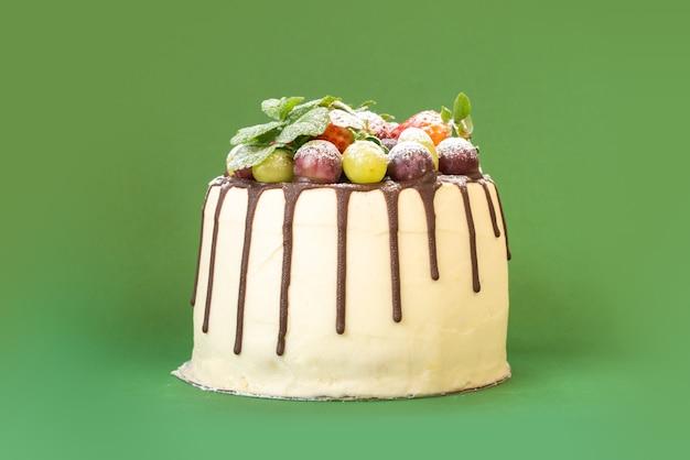 Delicioso bolo caseiro de chocolate branco com frutas sobre fundo isolado