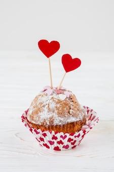 Delicioso bolo com corações vermelhos em varas