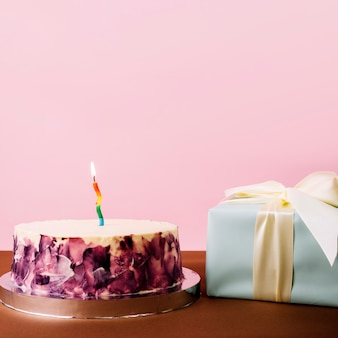 Delicioso bolo com vela iluminada e caixa de presente embrulhada contra fundo rosa