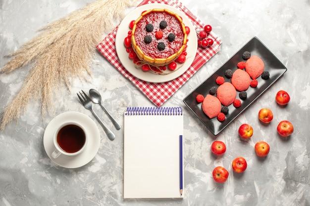 Delicioso bolo cremoso com cobertura vermelha e biscoitos de cima, juntamente com uma xícara de chá na superfície branca.
