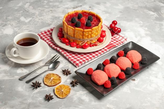 Delicioso bolo cremoso com cobertura vermelha e biscoitos, junto com uma xícara de chá na superfície branca, vista frontal
