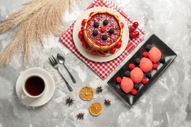 Delicioso bolo cremoso com cobertura vermelha e bolachas de cima, juntamente com uma xícara de chá na superfície branca, bolo biscoito açúcar doce torta de frutas