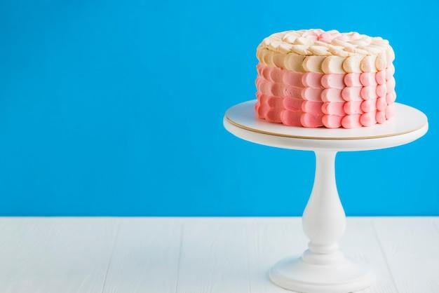 Delicioso bolo de aniversário com cakestand na frente da parede azul