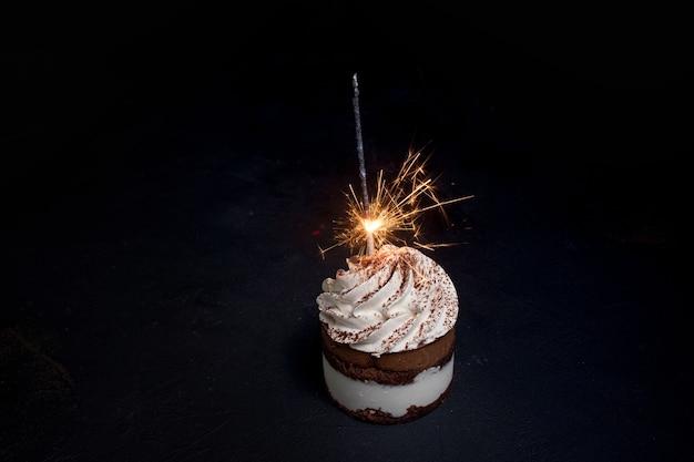 Delicioso bolo de aniversário com vela de fogo de artifício na mesa contra um fundo escuro.