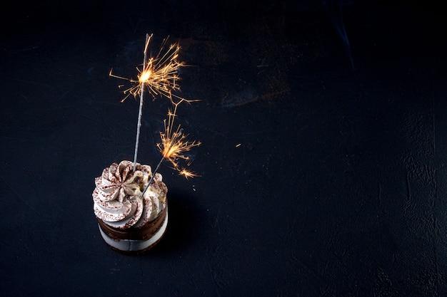 Delicioso bolo de aniversário com vela de fogo de artifício na mesa contra um fundo escuro