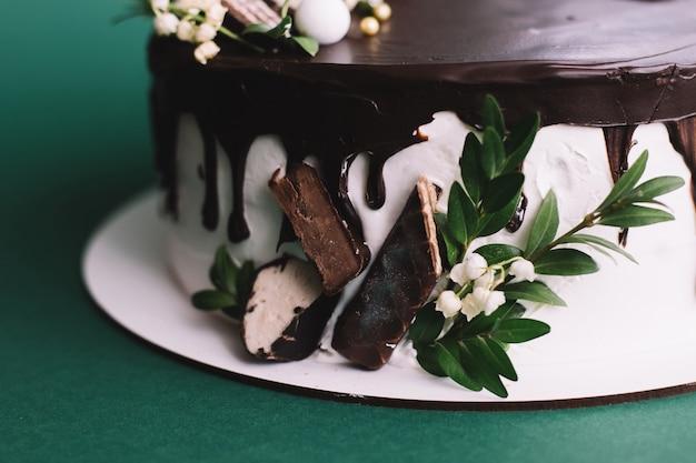 Delicioso bolo de chocolate caseiro com doces sobre fundo verde, close-up
