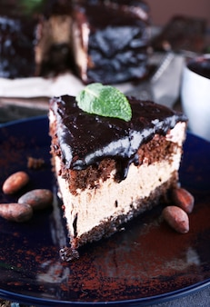 Delicioso bolo de chocolate com cobertura no prato na mesa