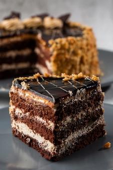 Delicioso bolo de chocolate com creme de coco branco no prato na mesa sobre fundo de mármore. papel de parede para café de pastelaria ou menu de café. vertical.