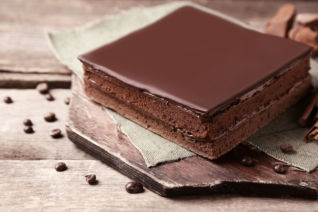 Delicioso bolo de chocolate com grãos de café em fundo de madeira