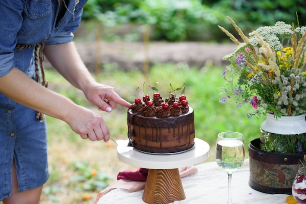 Delicioso bolo de chocolate decorado com cerejas com um copo de vinho branco