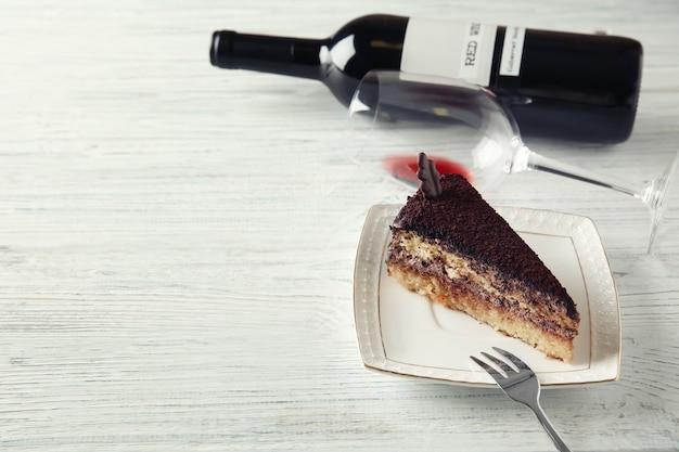Delicioso bolo de chocolate e vinho tinto na mesa de madeira branca