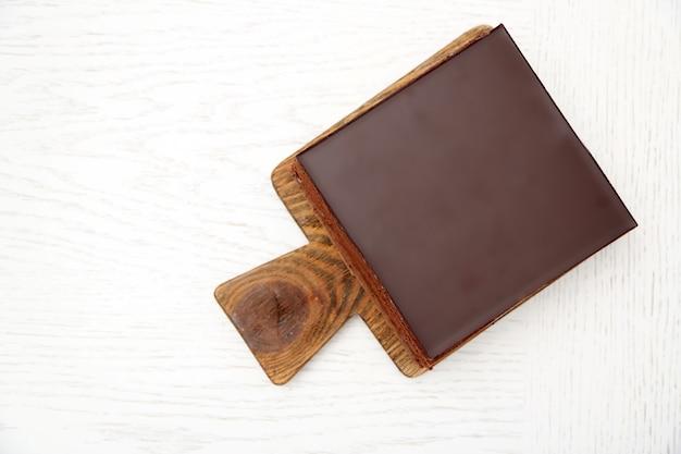 Delicioso bolo de chocolate em uma tábua de madeira isolado no branco