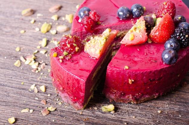 Delicioso bolo de framboesa com morangos frescos, framboesas, mirtilo, groselhas e pistachios