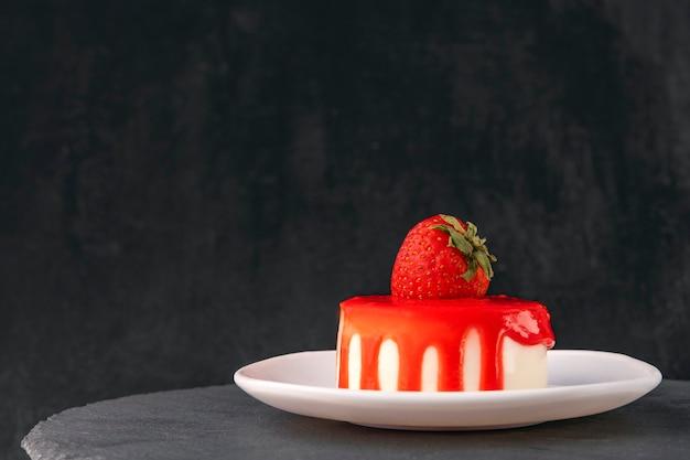 Delicioso bolo de frutas com morangos frescos em fundo preto. vista lateral. bolo de morango apetitoso.