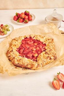 Delicioso bolo de galata com ruibarbo e morango com ingredientes em uma mesa branca
