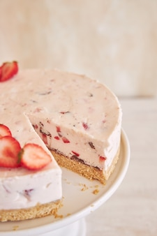 Delicioso bolo de iogurte gelado com fundo de biscoito e morangos