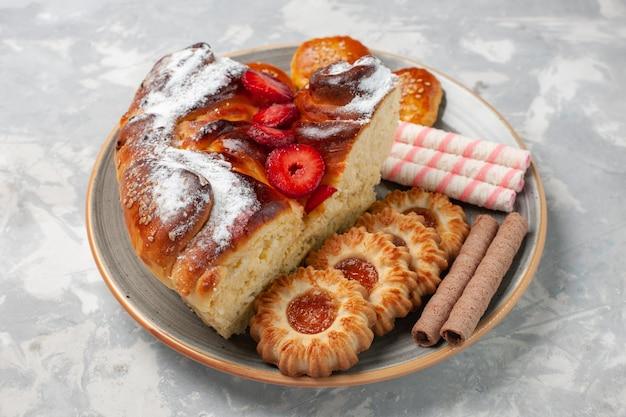 Delicioso bolo de morango com biscoitos e bolinhos na mesa branca.