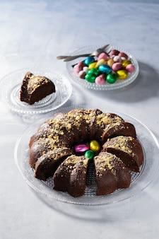 Delicioso bolo de páscoa chocolate com ovos de páscoa coloridos e chocolate na luz de fundo