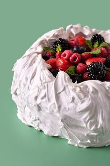 Delicioso bolo de pavlova com merengue coberto e frutas frescas sobre fundo verde