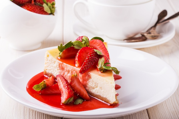 Delicioso bolo de queijo caseiro com morangos na mesa de madeira branca.