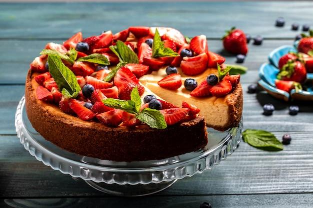 Delicioso bolo de queijo com frutas na mesa close-up.