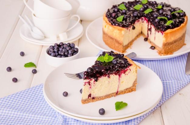 Delicioso bolo de queijo creme com raspas de limão e geléia de mirtilo em uma placa em madeira branca