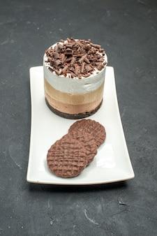 Delicioso bolo de vista frontal com chocolate e biscoitos em prato retangular branco no escuro